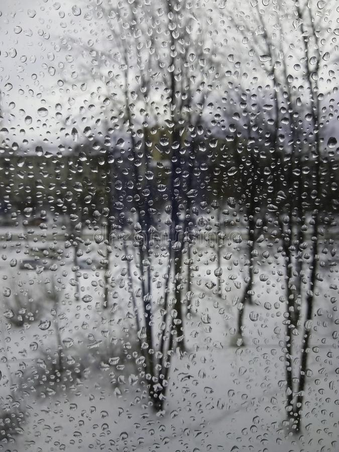 Raindrops on the glass, rain in the new year, rain with snow, wet weather, rainy weather, depression, gray sky royalty free stock image