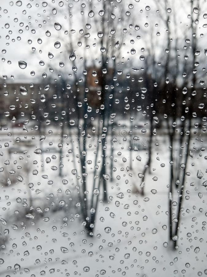 Raindrops on the glass, rain in the new year, rain with snow, wet weather, rainy weather, depression, gray sky stock photography