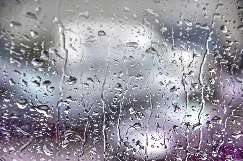 Raindrops on glass. Raindrops creating a pattern on a glass window, with unrecognizable shapes behind it, on a rainy day in Iceland royalty free stock images