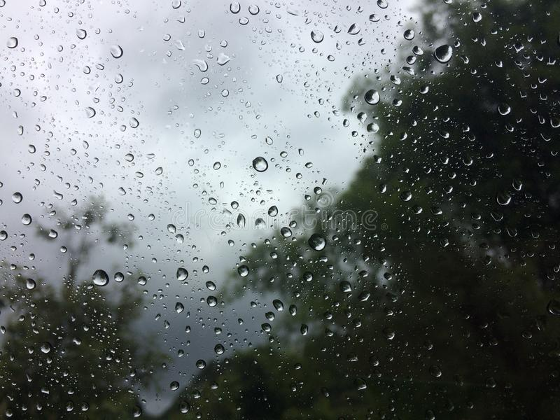 Raindrops on the glass. Raining with raindrops on glass and storm outside window royalty free stock images