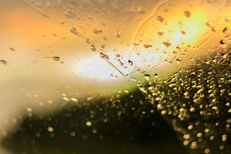 Raindrops on the glass. Sun rays and forest. Car windshield stock image