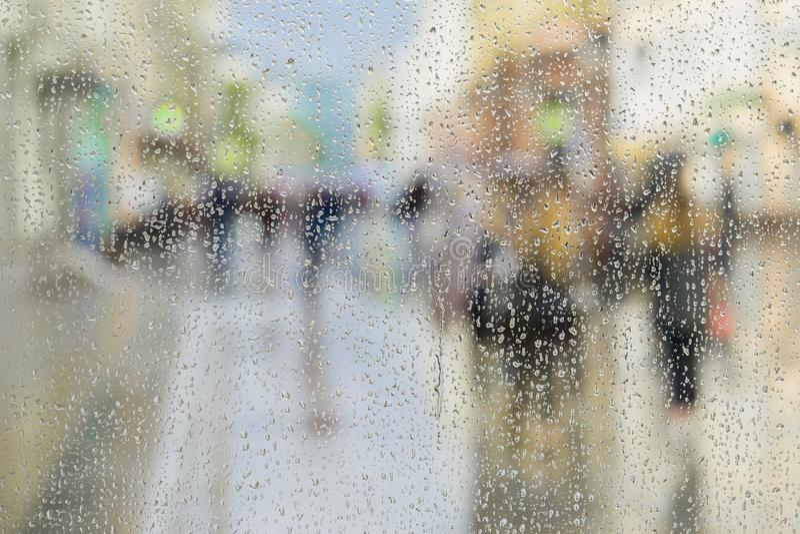 Raindrops na nadokiennym szkle, ludzie chodzą na drodze w deszczowym dniu, zamazany ruchu abstrakta tło Pojęcie zakupy zdjęcie royalty free