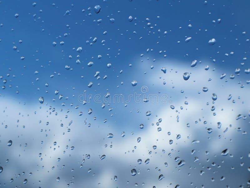 Raindrops na szkle przeciw niebieskiemu niebu z chmurami Jasny niebieskie niebo z cumulusem i chmur pierzastych chmurami pogodna  zdjęcia stock