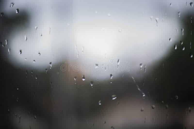 Raindrops p? ett f?nster Regnigt f?nster p? natten mörkt - blått vått, tappar av vattenregn på exponeringsglasbakgrund begrepp av arkivfoto