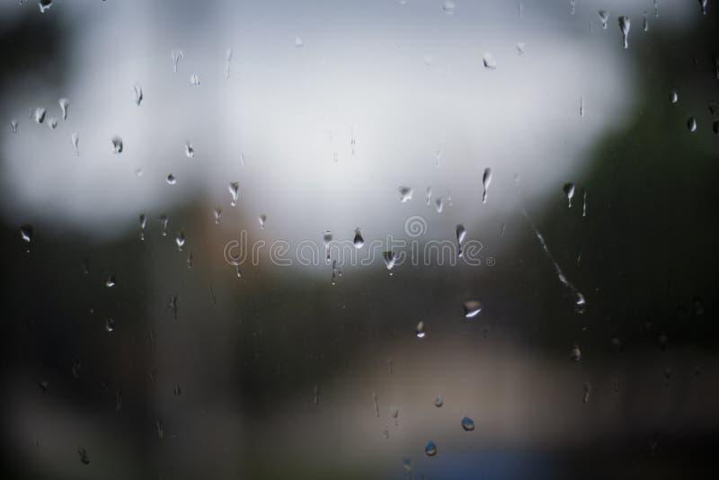 Raindrops p? ett f?nster Regnigt f?nster p? natten mörkt - blått vått, tappar av vattenregn på exponeringsglasbakgrund begrepp av arkivbild