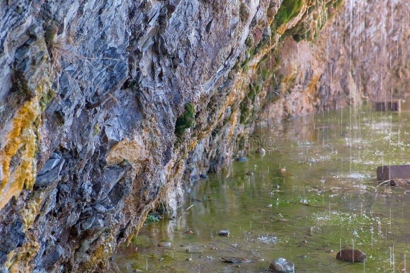 Raindrops przepływu puszek od skał w halnym jeziorze Piękne skały zawalają się z mech, w górę widoku zdjęcie royalty free