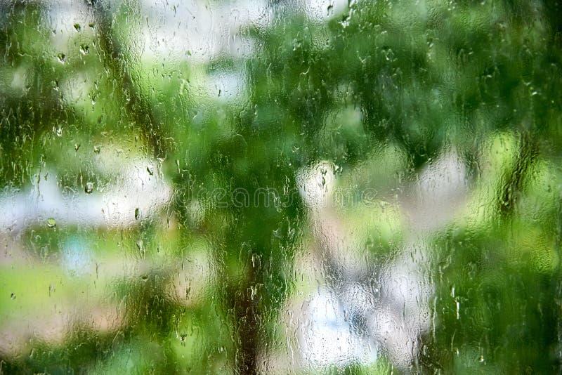 Raindrops przep?ywu puszek nadokienny szk?o i myje daleko od brud na zielonym tle zdjęcia royalty free