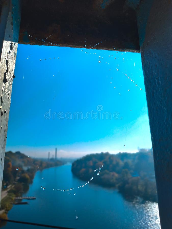 Raindrops on a spider web on the bridge beautiful river nature blue sky city royalty free stock photos