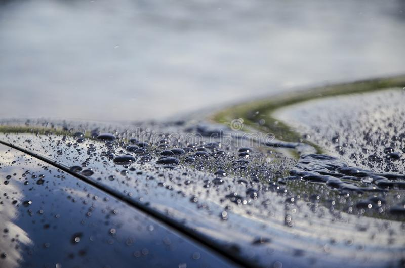 Raindrops or water droplets on the surface of the car. Hydrophobic property after the application of nano-ceramics. Abstract background and water texture for stock photography