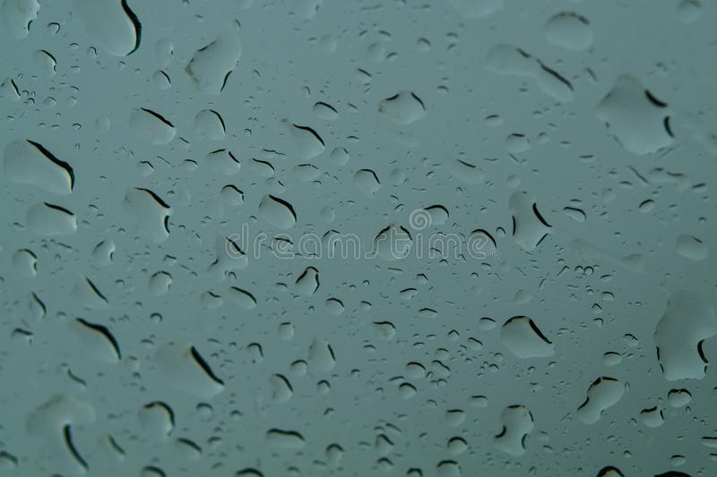 Raindrops on the window close up. rain drops on the glass macro. water drops falling down on window. rainy day. Wet glass. raindrops trickle down, abstract royalty free stock photo