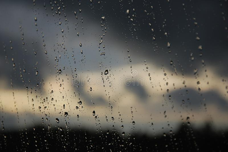 Raindrops on the window. Cloudy rainy weather. Raindrops on the window pane. Black, gray, white gradient on blurry background. Cloudy rainy weather outside the stock image