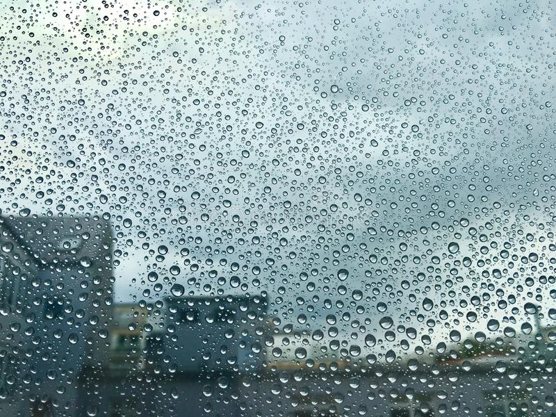 Raindrops on a window. Cloudy sky and building appear in the background stock photo