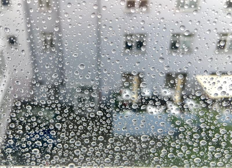 Raindrops on a window. Cloudy sky and building appear in the background stock images