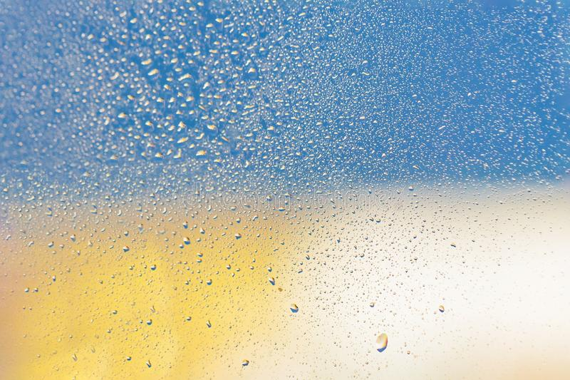 Raindrops on window glass. Blue yellow light background stock images
