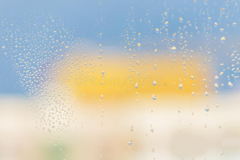 Raindrops on window glass. Blue yellow light background royalty free stock images