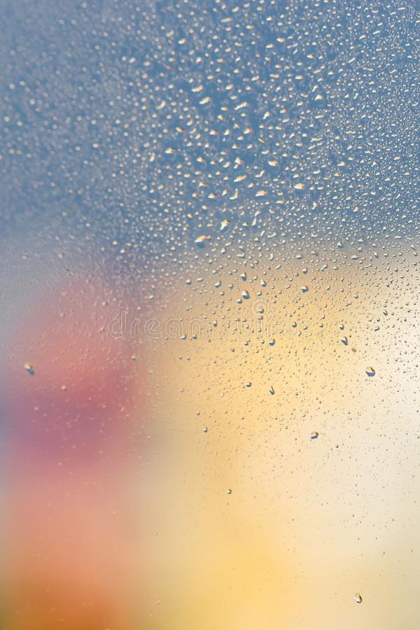 Raindrops on window glass. Gray, pink, yellow background, copy space. Raindrops on window glass. Gray, pink and yellow background. Copy space royalty free stock images