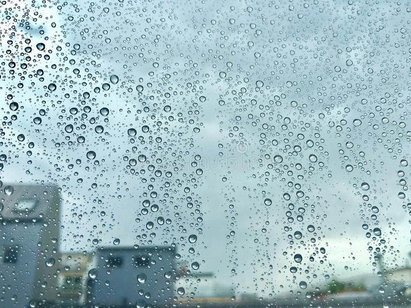 Raindrops on a window. Cloudy sky and building appear in the background royalty free stock images