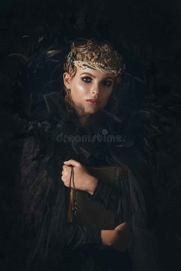 Rainha da escuridão no traje preto da fantasia no fundo gótico escuro Modelo da beleza da alta-costura com composição escura fotos de stock