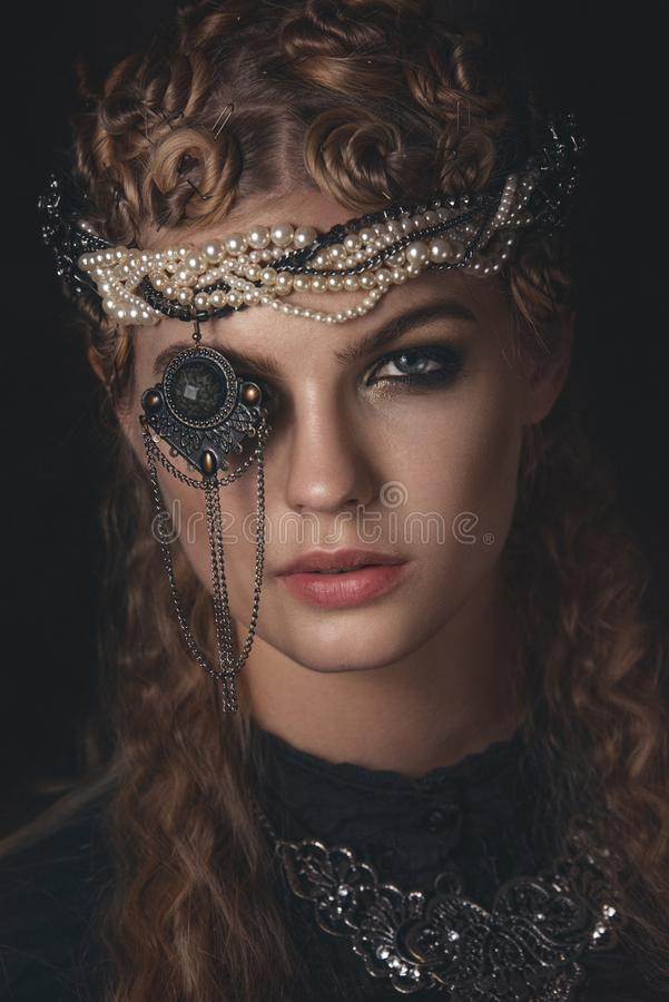 Rainha da escuridão no traje preto da fantasia no fundo gótico escuro Modelo da beleza da alta-costura com composição escura imagem de stock