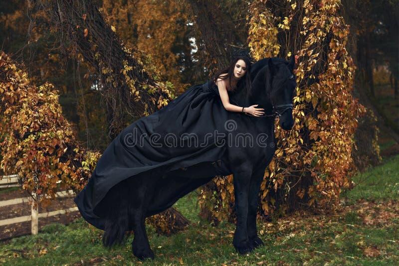 A rainha da viúva negra da bruxa abraça seu cavalo preto em uma floresta da obscuridade do horror fotografia de stock royalty free