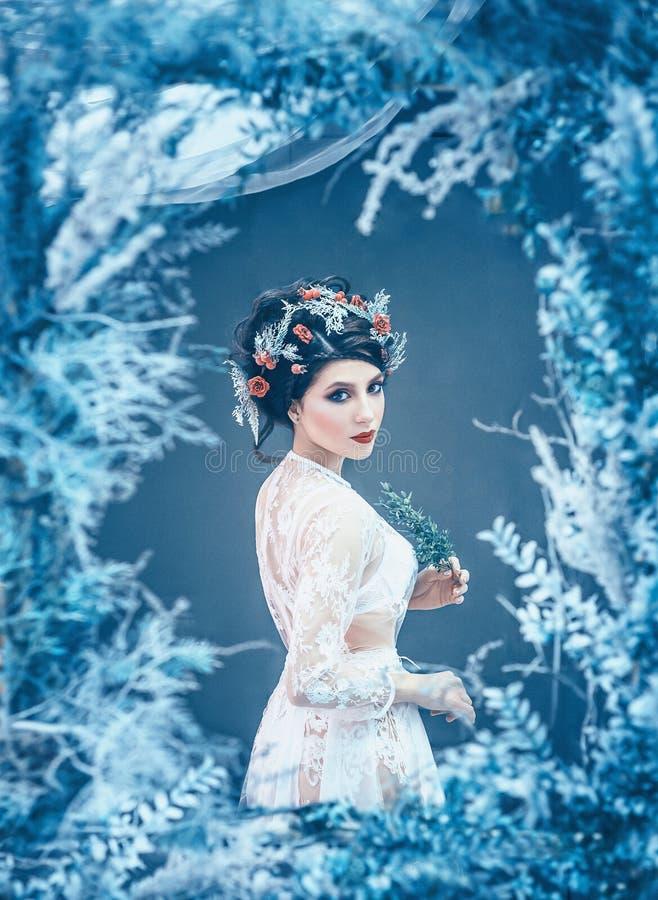 Rainha majestosa orgulhosa do inverno e do frio eterno no vestido branco longo com o cabelo recolhido escuro decorado com rosas c fotos de stock