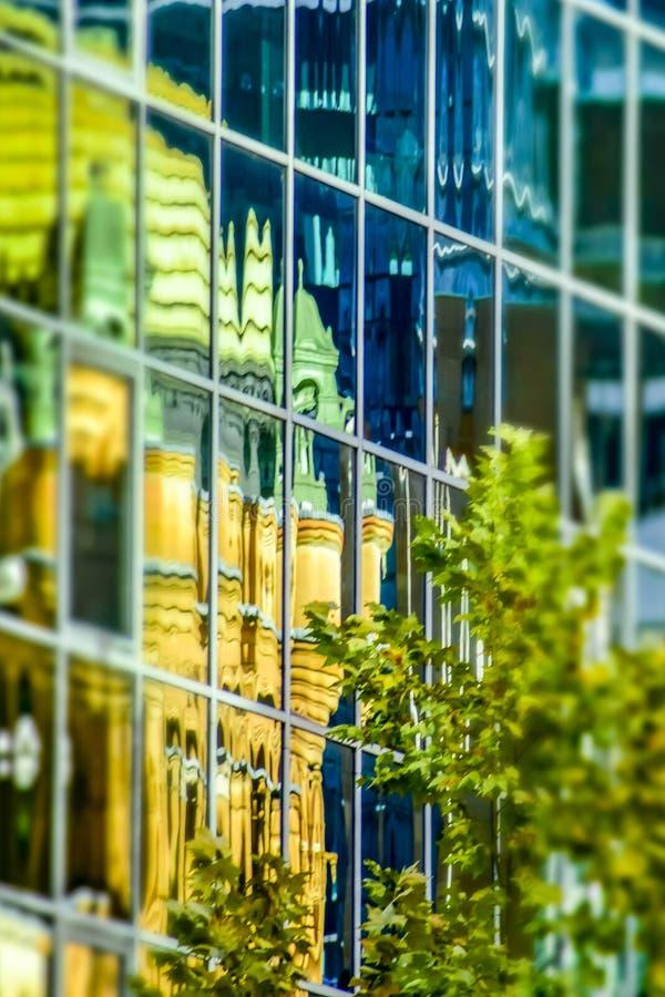 A rainha Victoria Building refletiu na construção alta de vidro moderna da elevação, efeito da câmera do brinquedo, centro da cid imagem de stock