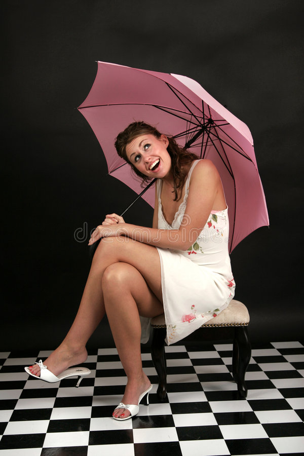 Is it raining?. Beautiful young woman in white dress sitting under pink umbrella and checking to see if it is raining royalty free stock photography