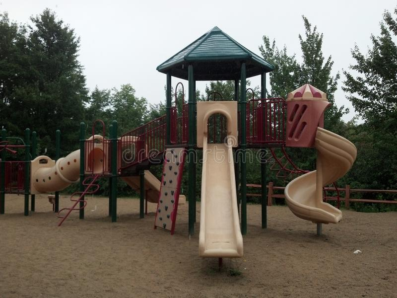 Raining on the playground. Dismal day on the empty wet playground in the rain royalty free stock photos