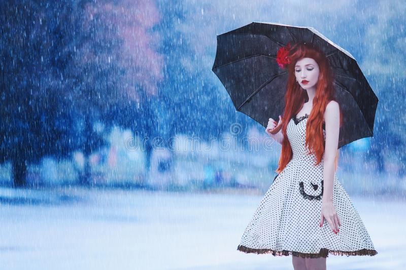 Raining weather. Autumn rain. Sad lonely girl in stress in dress hold umbrella. Raining in city. Umbrella against blue background royalty free stock photography