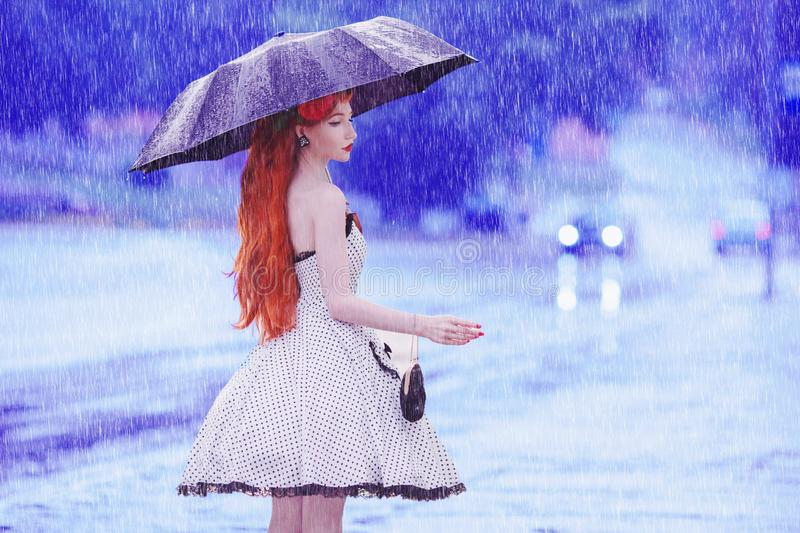 Raining weather. Autumn rain. Sick girl in depression in dress hold umbrella. Umbrella protection against street. Lonely woman wi stock photo