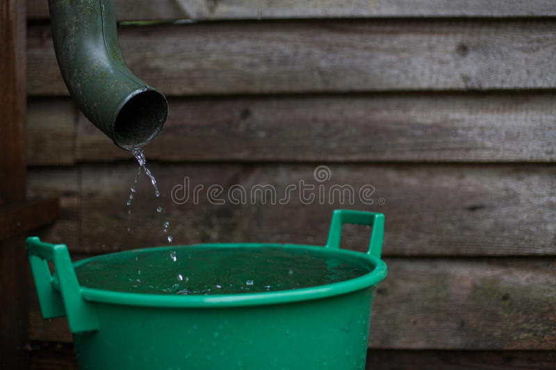 Rainwater shooting from a gutter into a water collecting reservoir. Rainwater gushing down from a gutter in a flooding season into a water collecting reservoir stock images