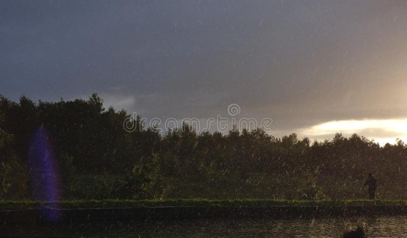 Rainy afternoon - rain started pouring down next to the canal with the sun shining in the distance, photo taken in the UK royalty free stock photo