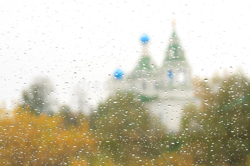 Rainy autumn day, view of the autumn forest and the church through the wet window. Autumnal sad landscape stock images