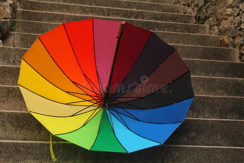 Rainbow umbrella - a bit of colours in autumn rain. Rainy autumn days - colourful umbrella royalty free stock images