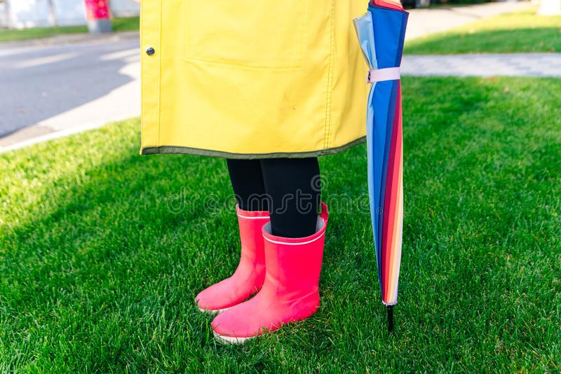 Yellow raincoat. Rubber pink boots against. Conceptual image of legs in boots on green grass. Rainy autumn. Rubber pink boots against. Conceptual image of legs royalty free stock photography