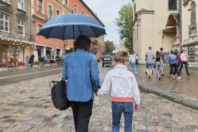 Woman with child girl walking under an umbrella in street. Rainy autumn weather in city, woman with child girl walking under an umbrella in street, rear view royalty free stock images