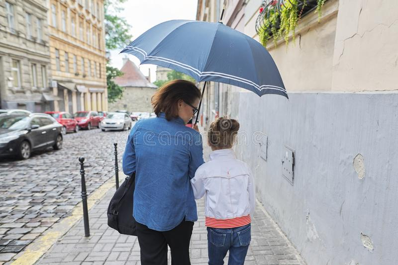 Woman with child girl walking under an umbrella in street. Rainy autumn weather in city, women with child girl walking under an umbrella in street, rear view stock images