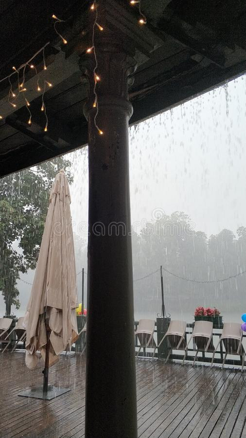 Rainy birthday party on the river. Patio stock images