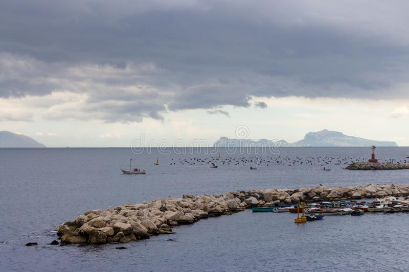 Rainy clouds over Adriatic sea with island silhouette and moored boates. Bad weather concept. royalty free stock photos