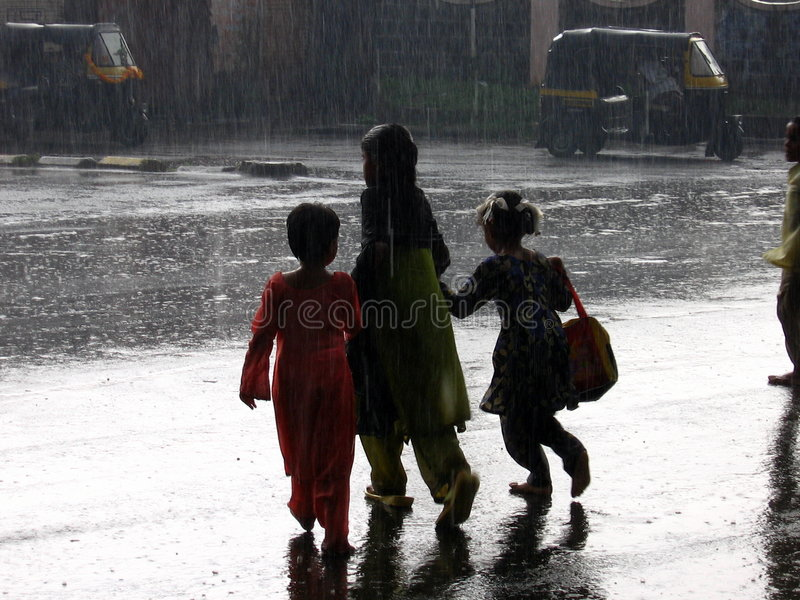 The Rainy Crossing. Three poor children try to cross a busy street on a rainy day in India stock photo