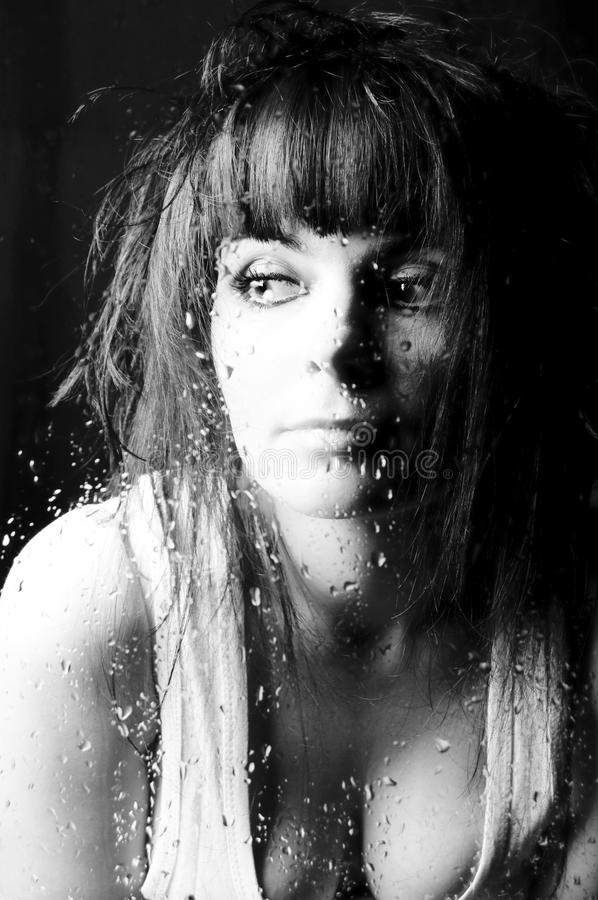 Rainy day. The beautiful woman looks through window. On which glass drops of a rain flow and dreams royalty free stock photos