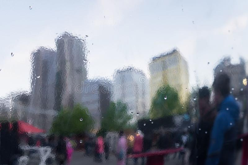 Rainy day in city. Selective focus on the raindrops. Distorted reflection of city and people on metal surface royalty free stock photo