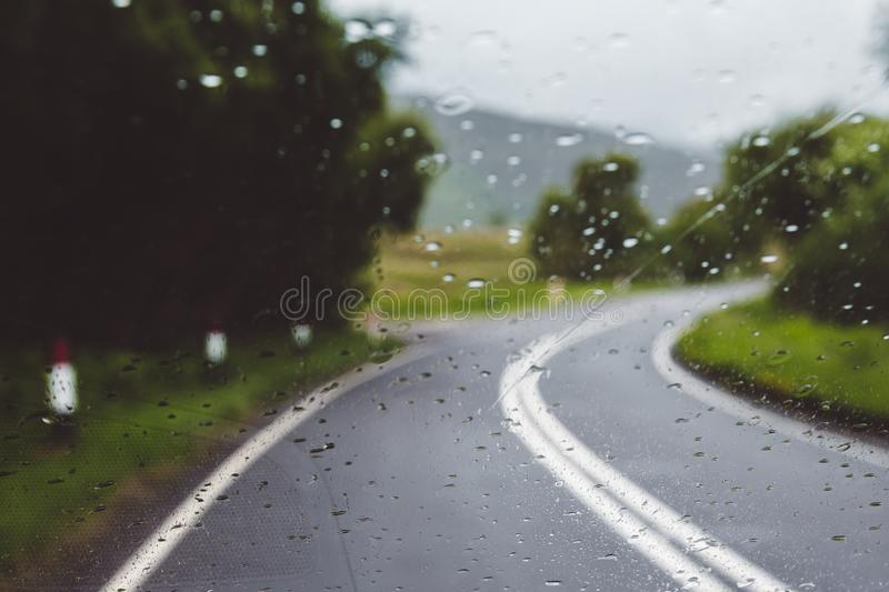 Rainy day driving on a single carriageway in slippery conditions. Blurred out of focus royalty free stock image