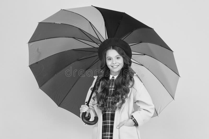 Rainy day fun. Happy walk under umbrella. Enjoy rain concept. Kid girl happy hold colorful rainbow umbrella. Rainy. Weather with proper garments. Bright royalty free stock image