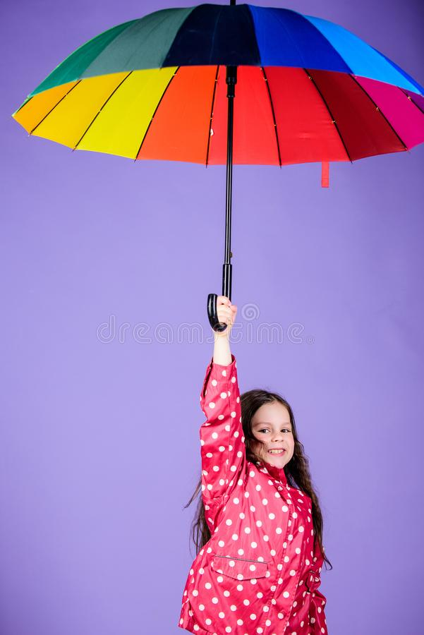 Rainy day fun. Happy walk under umbrella. Enjoy rain concept. Kid girl happy hold colorful rainbow umbrella. Rainy stock image