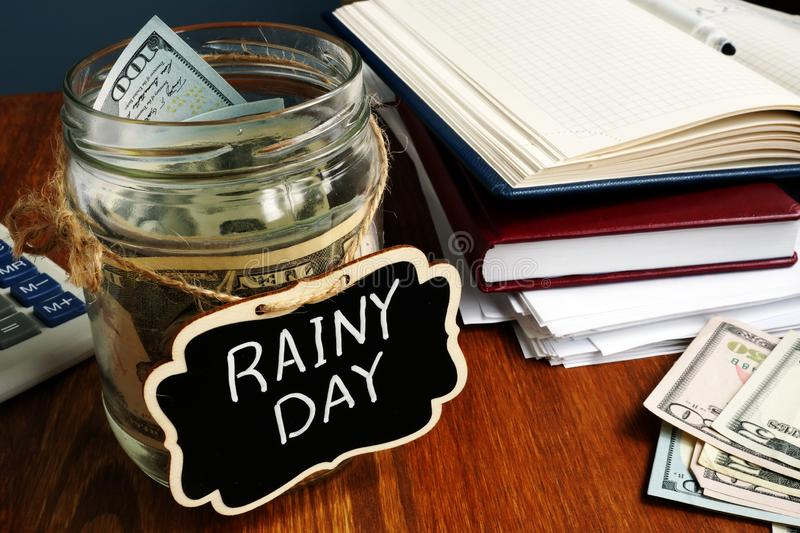Rainy Day Fund label on the jar with money stock images