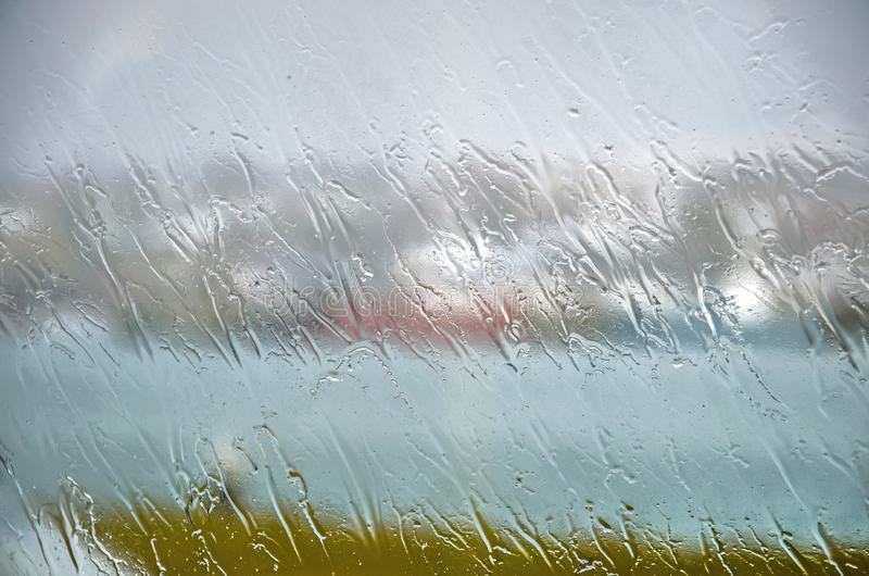 A rainy day in Hafnarfjordur. Falling rain creating stripe patterns on the glass of a window on a rainy day in Hafnarfjordur, Iceland, with behind it barely stock photo