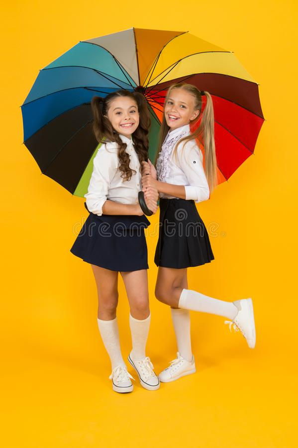 Rainy day. Happy childhood. School time. Rainbow umbrella. Colorful life. Schoolgirls happy big umbrella. Fall weather. Forecast. Place for both of us. Fashion royalty free stock images