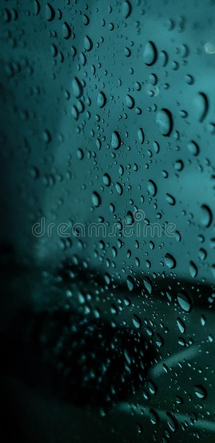 Rainy Day: I love the rain, it calms me down and is very peaceful to watch as the droplets collide with the glass window. stock photography