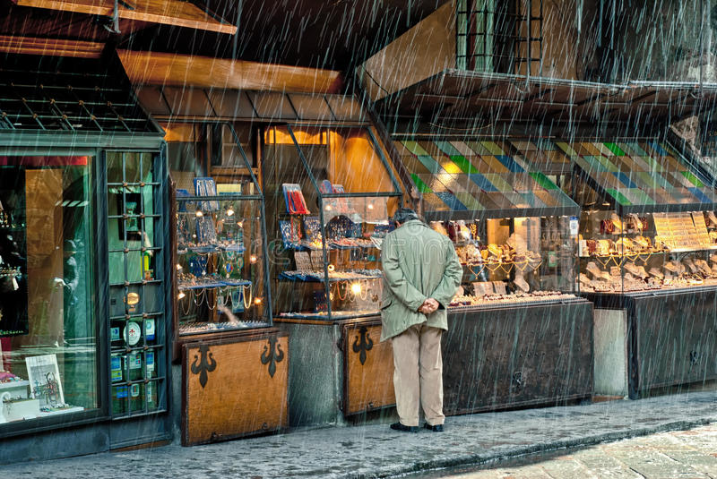 Rainy day on Pontevecchio, Florence, Italy. Man looking through a window of one of the famous shops on Pontevecchio (Old Bridge), Italy. Pontevecchio is a bridge